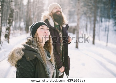 A loving happy young couple walking in the winter woods. Rustic style - stock photo