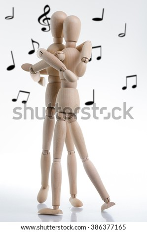 A loving hug is shared between two wooden characters, with blurred music notes in the background.