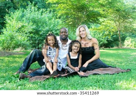 A loving mixed race family enjoying the park - stock photo