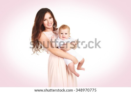 A loving mother in a dress hugs a young child isolated - stock photo