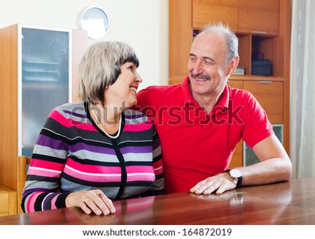 A loving senior couple inside their home.
