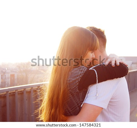 A loving young couple embracing on the bridge - stock photo