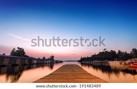 A low angle perspective of an empty dock on the bay at a local marina with boats an storage units.  Long exposure.  - stock photo