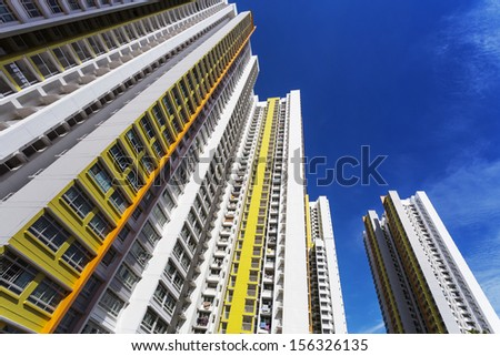 A low angle shot of a new colorful high rise apartment against the sky.