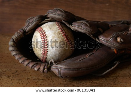 A low contrast image of a well used hardball and glove for those who love the sport of baseball.