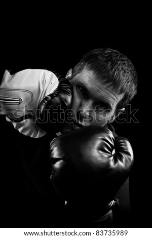 A Low key black and white image of a man in a boxing match being hit in the face