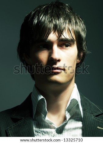 A low-key portrait about a trendy handsome guy who has a glamorous look. He is wearing a white shirt and a black suit. - stock photo