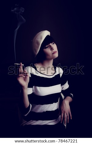 A low-key portrait of an attractive woman smoking a cigarette and wearing a beret. - stock photo
