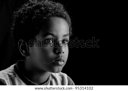 A low key portrait picture of a young Ethiopian boy . - stock photo