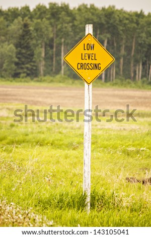 A low level crossing sign in the countryside