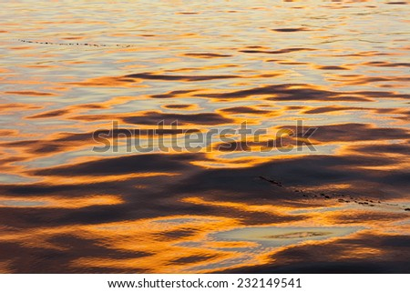A low, orange sunset reflects off the surface of the ocean, creating a beautiful wavy, natural pattern - stock photo