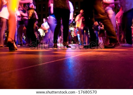 A low shot of the dance floor with people dancing under the colorful lights - stock photo