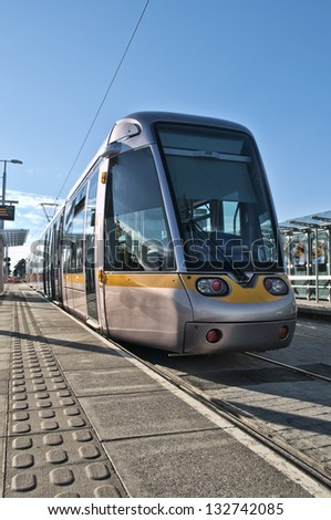 A Luas tram train pulling into a station in South County Dublin, Ireland. - stock photo