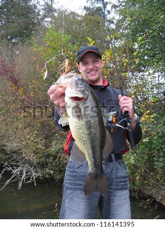 A lucky fisherman holding a largemouth bass - stock photo