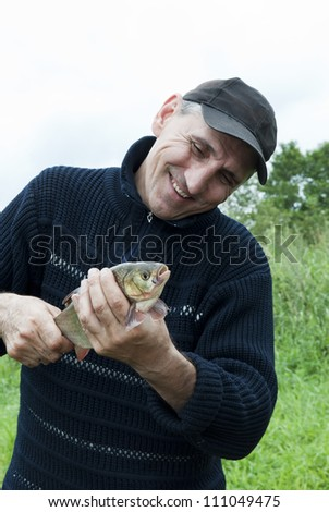 A lucky fisherman with a chub - stock photo