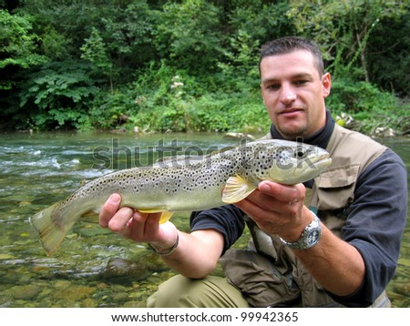 A lucky trout fisherman - stock photo