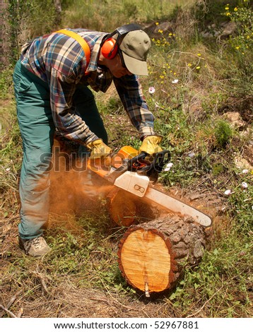 A lumberjack in action in full protective gear - stock photo