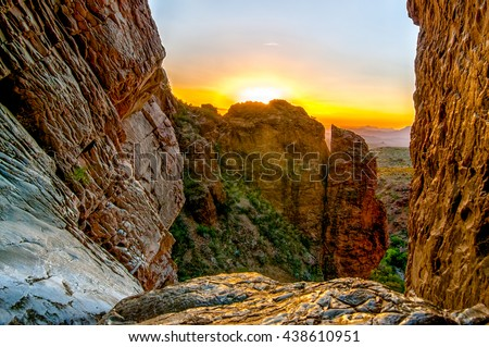 A luminous sunset over the desert with mountains in the distance, from a mountain, with a valley and unique ecosystem below it during the summer at the Window Pouroff Trail in Texas.
