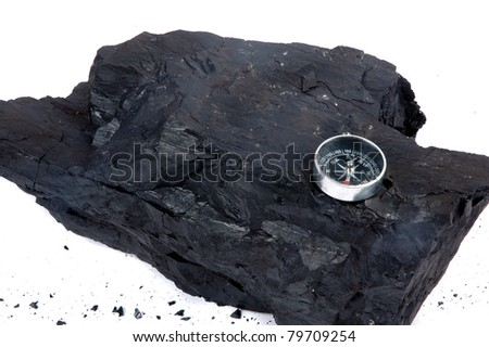 a lump of coal and compass - stock photo