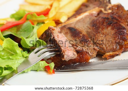 A lump of T-bone steak on a fork with the meal in the background