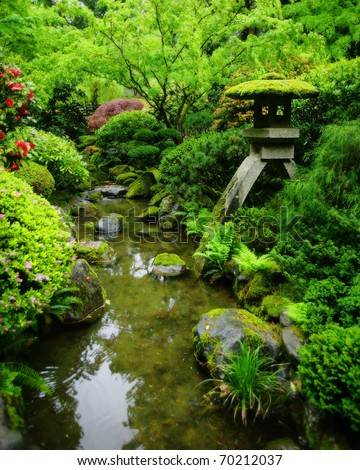 A lush green Japanese garden with Japanese lantern, and moss covered rocks. - stock photo