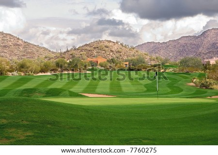 A lush, manicured Arizona golf course with clouds over mountains - stock photo