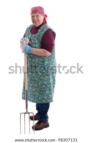 A lusty female senior with pitchfork  looks to viewer - stock photo