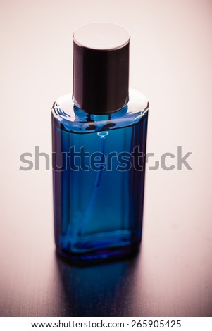 a luxurious blue crystal perfume bottle on a wooden surface - stock photo