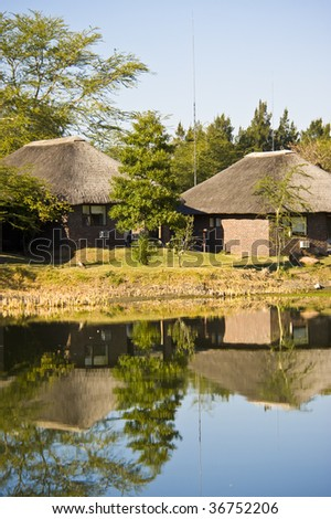 A luxurious camp in a wildlife park with some accommodation around a small lake.