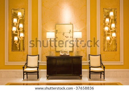 A luxurious dresser with a classic lamps, sculpture and a mirror in a hallway with two armchairs. - stock photo
