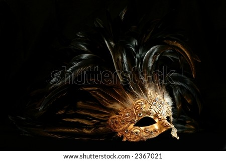 A luxurious golden mask with long feathers on a black background