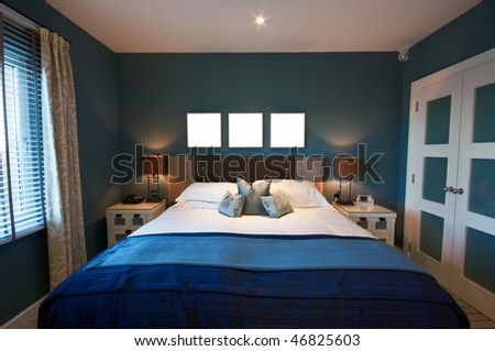 A luxurious modern bedroom on a bright morning. Wardrobe to one side, with window to the other, and three blank square boxes above the bed for your design/text. - stock photo