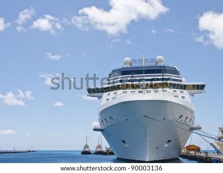 A luxury cruise ship anchored at a pier with two tug boats - stock photo