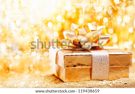 A luxury gold Christmas gift tied with an ornamental bow against a golden bokeh of sparkling festive lights with copyspace for your seasonal greeting - stock photo