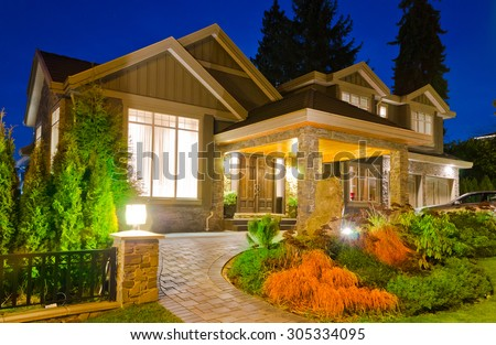 A luxury house with driveway  in suburbs at dusk, night, dawn time in Vancouver, Canada. - stock photo