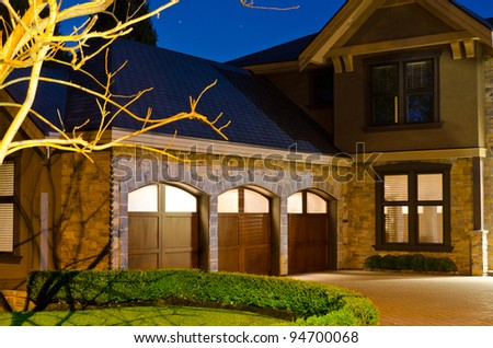 A luxury house with  three  garage doors in suburbs at dusk in Vancouver, Canada - stock photo