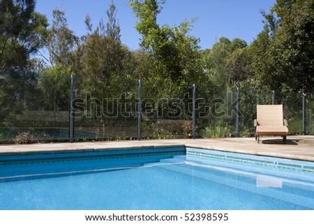 A luxury outdoor pool with deck chair beside it