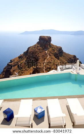 A luxury swimming pool situated in the town of imerovigli on the greek island of santorini with a view of skaros in the background. - stock photo