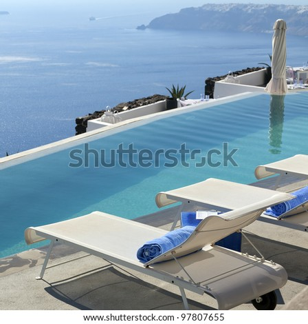 A luxury swimming pool situated in the town of imerovigli on the greek island of santorini with a view of oia in the distance. - stock photo