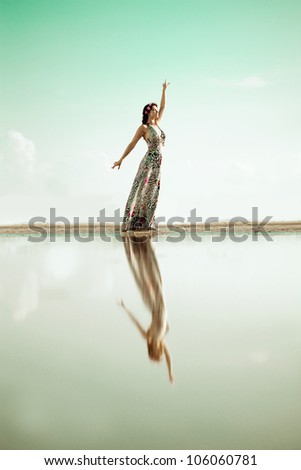 A luxury woman with arms raised outdoors by the ocean