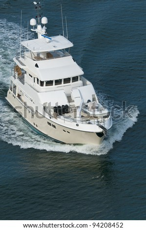 A luxury yacht moving through calm water in the Pacific Ocean. - stock photo