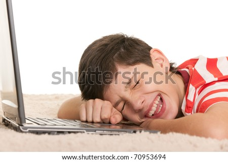A lying boy is crying with joy after computer game; isolated on the white background - stock photo