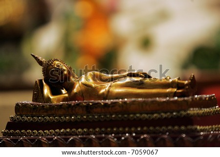 A Lying Buddha statue is on display at a temple. - stock photo