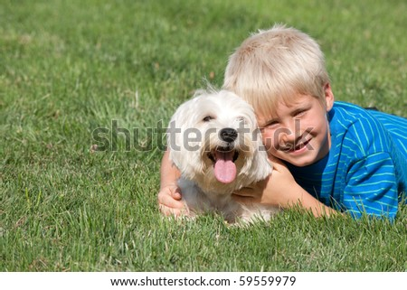 A lying on the grass smiling boy is hugging his pet