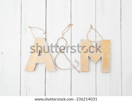 A&M letters made by hands of cardboard and metal wire. Christmas tree toys or wedding decorations decorated on a white wooden background - stock photo