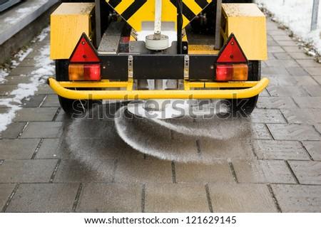 A machine is sprinkling salt on a sidewalk - stock photo