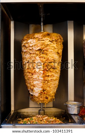 A machine slowly grills a skewered mass of chicken, a typical meat served inside a sandwich in the Middle East - stock photo