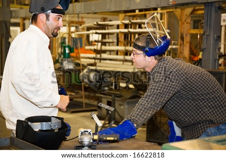 A machinist in a factory listens as his supervisor critiques metal working project.  Authentic and accurate content depiction in accordance with industry code and safety regulations. - stock photo
