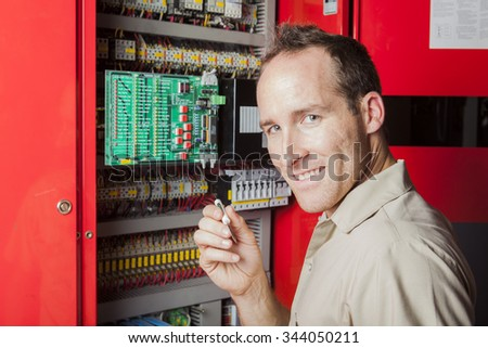 A machinist worker technicians at work adjusting lift with spanners in elevator hoistway - stock photo