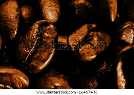 A macro closeup of freshly roasted coffee beans in a sepia tone.